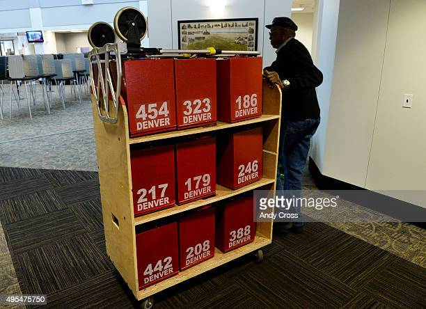 Ballot security worker for the Denver Elections Division David Williams pushes a cart of empty election boxes down a hallway to the elevator after...