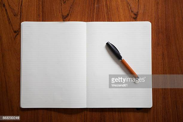 Ballpen lying on opened notebook
