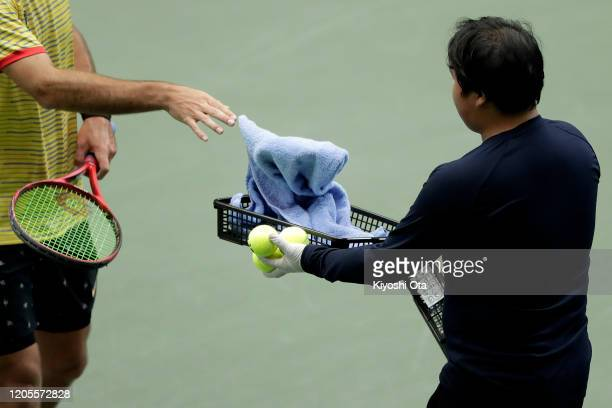 A ballperson uses a basket to receive a towel as preventive measures against novel coronavirus during the doubles match between Ben McLachlan and...
