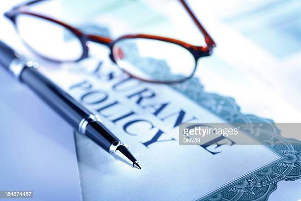 Ballpoint pen and eyeglasses on top of insurance policy