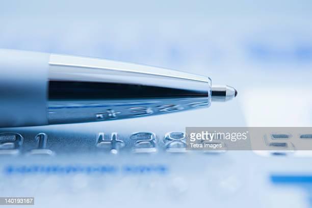 Ballpoint pen on credit card, studio shot