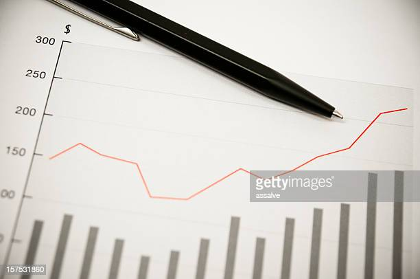 ballpoint pen pointing on chart graph histogram