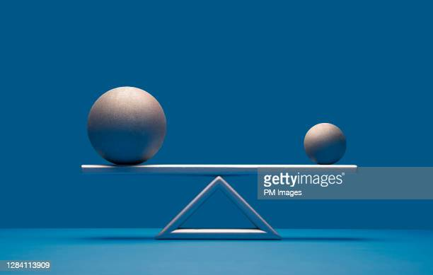 balls balancing on scale - equilibrio fotografías e imágenes de stock
