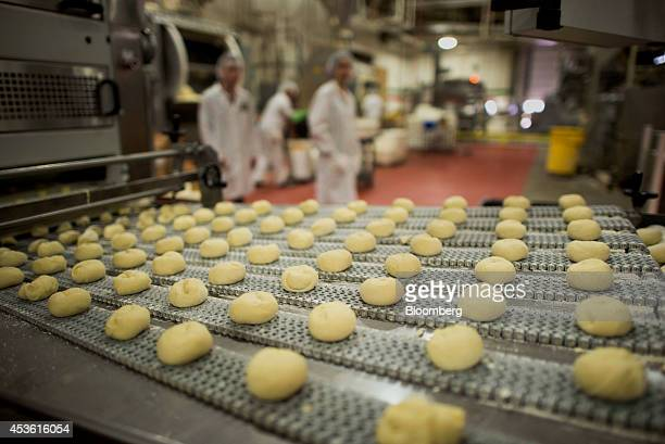 Balls of dough move on a conveyor belt before being baked in the oven at the Orlando Baking Co in Cleveland Ohio US on Wednesday Aug 13 2014 Wheat...