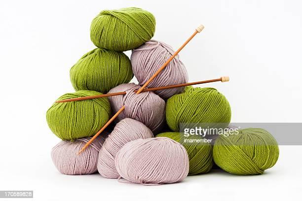 Balls of merino wool with bamboo knitting needles, white background