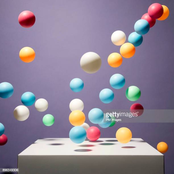 Balls of various color bouncing off of white box