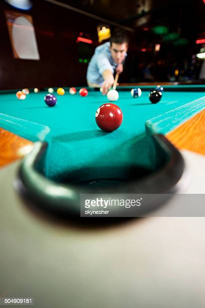 Balls on a pool table with man in the background