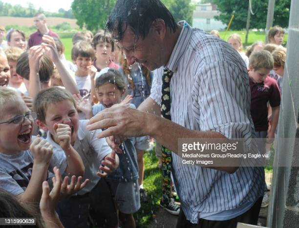 Bally, PASt. Francis Academy Principal Deacon Tom Murphy stands with water dripping off him after taking a salvo of water balloons from students and...