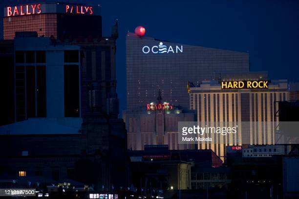 Bally's Ocean Resorts and Hard Rock Casino are illuminated at dusk despite being shuttered during the coronavirus pandemic on May 7 2020 in Atlantic...