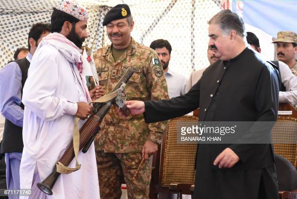 A Baloch militant hands over his weapon and surrenders to Baluchistan province Chief Minister Sardar Sanaullah Khan Zehri in Quetta on April 21 2017...