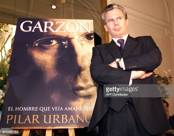 Baltasar Garzon the Spanish Judge who launched the legal pursuit of Chile's former dictator Augusto Pinochet stands next to the cover of a book about...