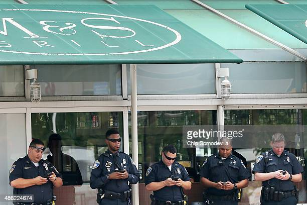 Baltimore City police check their mobile devices across Pratt Street from a demonstration at the Inner Harbor September 2 2015 in Baltimore Maryland...