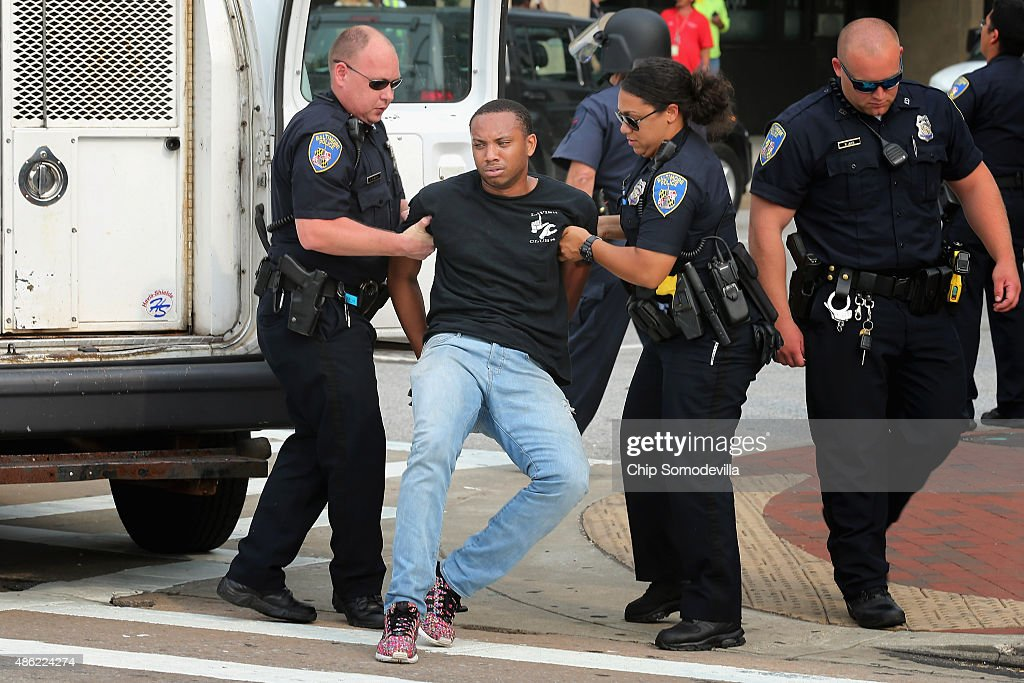 Baltimore City police officers lift activist Kwame Rose off the ground while arresting him during a demonstration at the Inner Harbor September 2, 2015 in Baltimore, Maryland. Rose said he was injured when he was hit by a car when demonstrators tried to shut down traffic during the pre-trial hearing for six police officers charged in the death of Freddie Gray. Earlier this year Gray, 25, suffered a severe spinal cord injury while in police custody and later died. His funeral was followed by rioting, looting and arson.