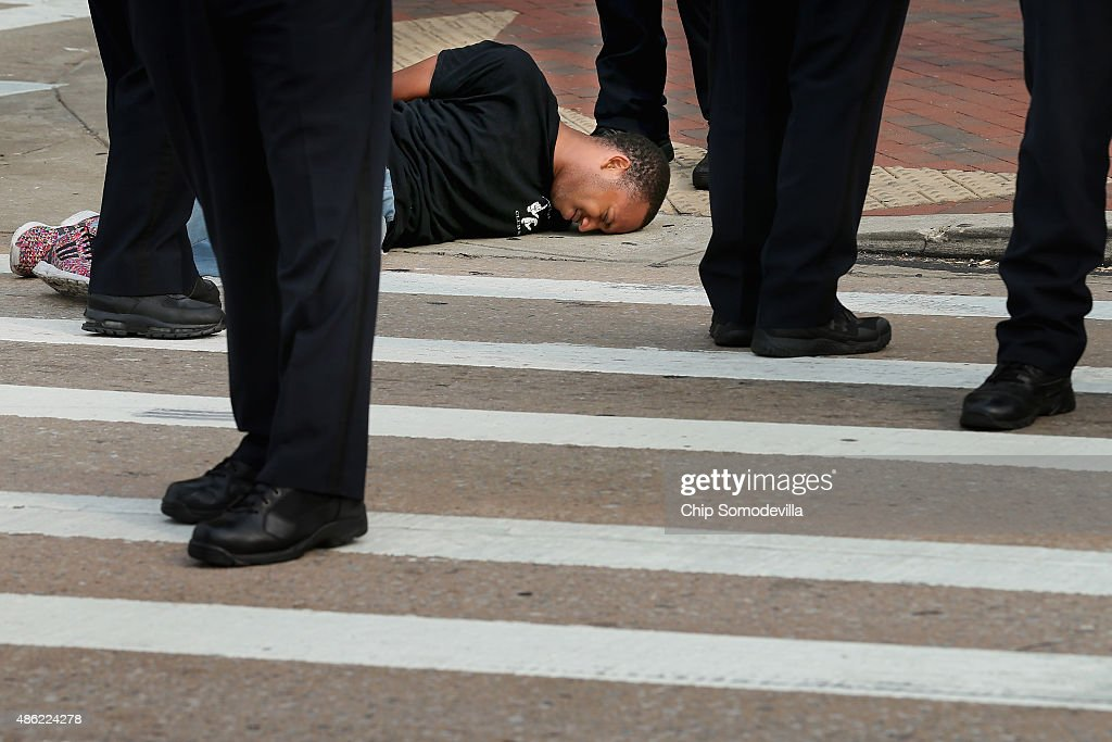 Baltimore City police officers stand around activist Kwame Rose as he was arrested during a demonstration at the Inner Harbor September 2, 2015 in Baltimore, Maryland. Rose said he was injured when he was hit by a car when demonstrators tried to shut down traffic during the pre-trial hearing for six police officers charged in the death of Freddie Gray. Earlier this year Gray, 25, suffered a severe spinal cord injury while in police custody and later died. His funeral was followed by rioting, looting and arson.