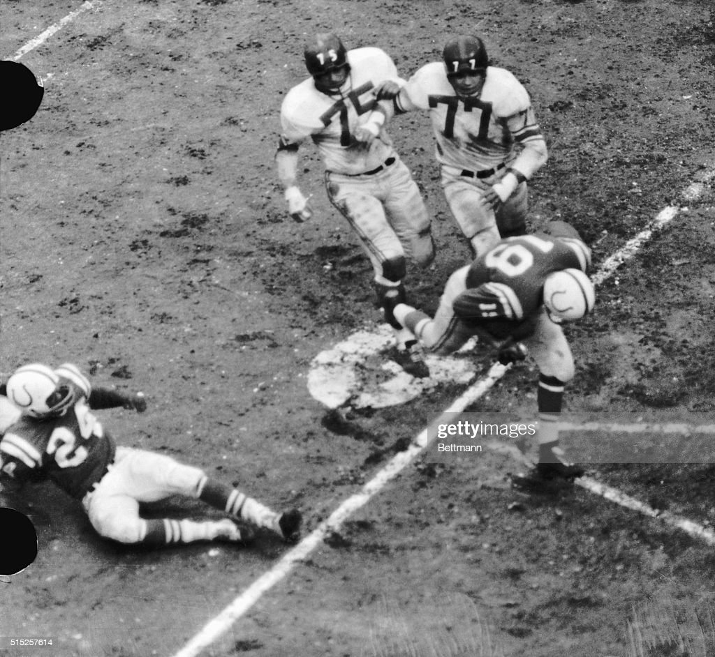 Baltimore Colts' Quarterback, Johnny Unitas (19), scoring a touchdown from the Giants' three-yard line in the fourth quarter of the NFL Championship game. Unitas crosses the line pursued by Jim Catcavage (75) and Rosey Brown (77) of the NY Giants. The Colts won their second straight NFL Championship game against the Giants, 31-16.