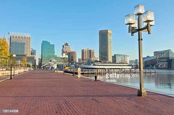 baltimore inner harbor skyline and paved waterfront promenade - baltimore stock photos and pictures