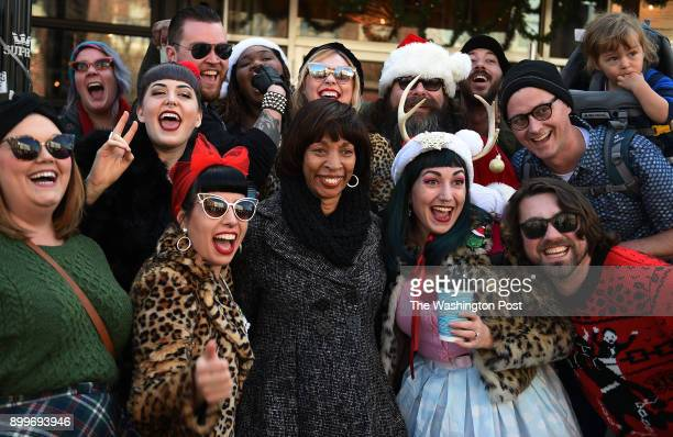 Baltimore Mayor Catherine Pugh poses with a cheering crowd for a quick photograph while marching in the Mayor's Annual Christmas parade in Hampden...