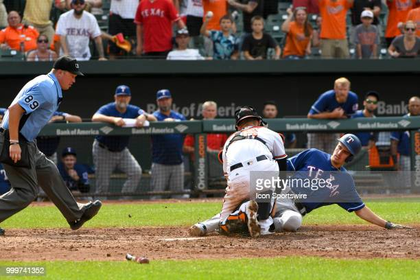 Baltimore Orioles catcher Caleb Joseph takes the throw to home to tag out Texas Rangers center fielder Carlos Tocci as home plate umpire Cory Blaser...