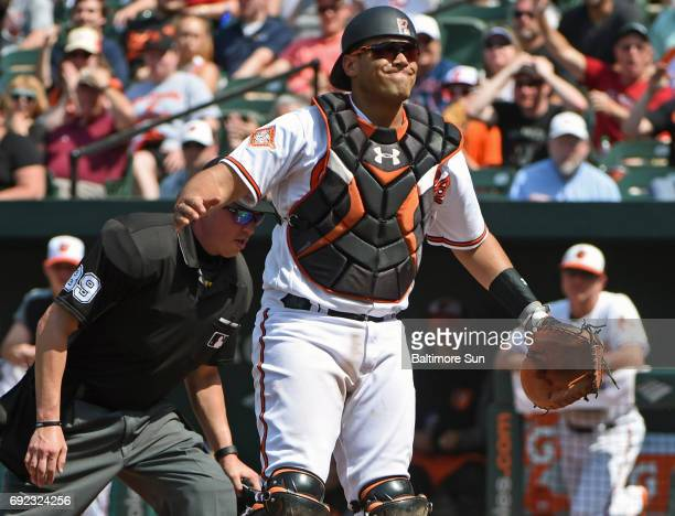 Baltimore Orioles catcher Francisco Pena reacts after his throwing error allows the Boston Red Sox's Mitch Moreland and Jackie Bradley to score the...