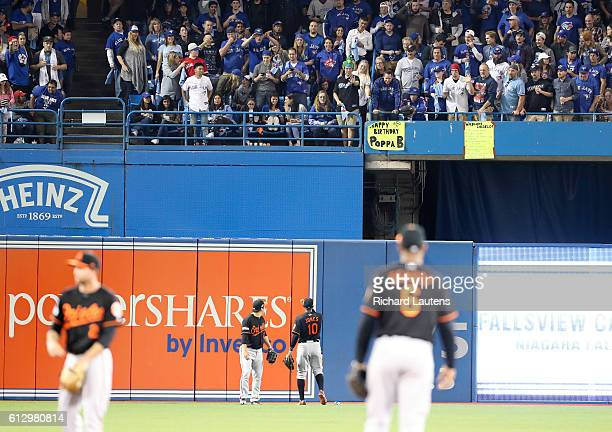 Baltimore Orioles center fielder Adam Jones and Baltimore Orioles left fielder Hyun Soo Kim have words with the fans in the outfield, one of whom...
