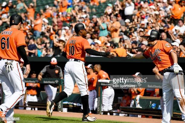 Baltimore Orioles center fielder Adam Jones is congratulated by third baseman Danny Valencia after scoring in the third inning during the interleague...