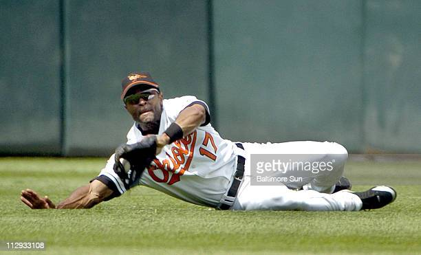 Baltimore Orioles center fielder Corey Patterson is unable to hold onto the ball after he made a diving catch on a ball hit by Philadelphia Phillies'...