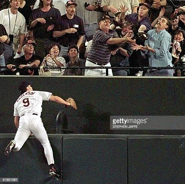 Baltimore Orioles centerfielder Brady Anderson tries but can only watch as a fan at upper right grabs Cleveland Indians player Manny Ramirez's tworun...