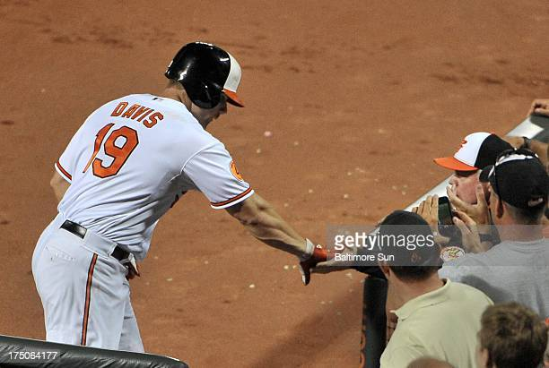 Baltimore Orioles' Chris Davis gets a handshake from manager Buck Showalter after he hitting a two run homer in the 6th inning against the Houston...