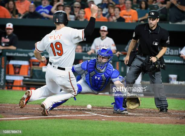 Baltimore Orioles' Chris Davis, left, scores as the ball gets away from Toronto Blue Jays catcher Reese McGuire in the fourth inning on Tuesday,...