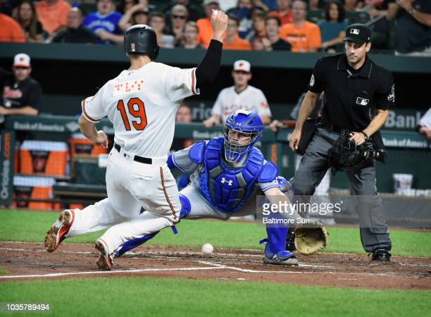 Baltimore Orioles' Chris Davis left scores as the ball gets away from Toronto Blue Jays catcher Reese McGuire in the fourth inning on Tuesday Sept 18...