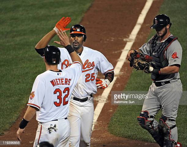 Baltimore Orioles' Derrek Lee center is congratulated by Matt Wieters left in front of Boston Red Sox catcher Jarrod Saltalamacchia right after Lee's...