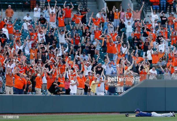 Baltimore Orioles fans cheer after left fielder Matt Joyce of the Tampa Bay Rays couldn't catch a ball hit by Manny Machado of the Baltimore Orioles...