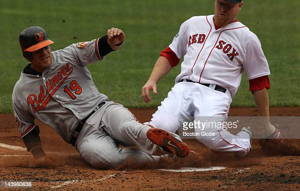 Baltimore Orioles first baseman Chris Davis slides safely into home plate ahead of Boston Red Sox starting pitcher Aaron Cook who was covering home...