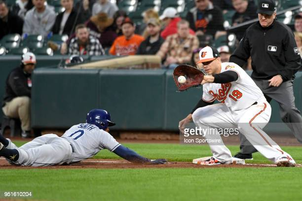 Baltimore Orioles first baseman Chris Davis takes a throw as Tampa Bay Rays center fielder Mallex Smith dives back to first base during the game...