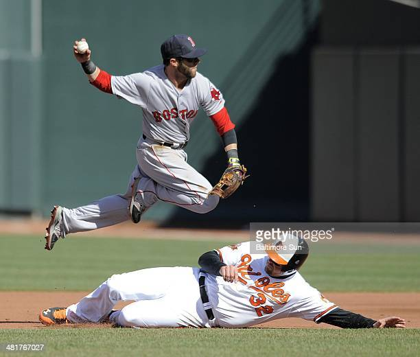 Baltimore Orioles' Matt Wieters slides under Boston Red Sox 2nd baseman Dustin Pedroia on a double play getting Delmon Young at first base during the...