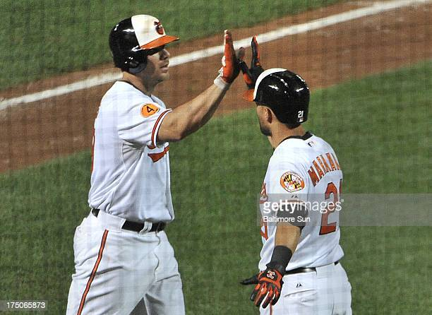 Baltimore Orioles Nick Markakis congratulates Chris Davis on his 6thinning homer against the Houston Astros at Oriole Park at Camden Yards in...