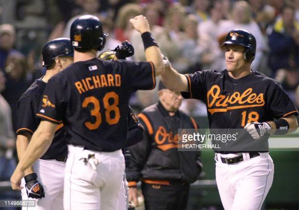 Baltimore Orioles player Jeff Conine is congratulated by his teammates at homeplate after hitting a grandslam homerun against Minnesota Twins pitcher...