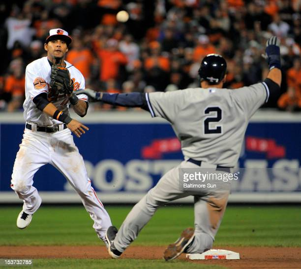 Baltimore Orioles second baseman Robert Andino throws over New York Yankees shortstop Derek Jeter but the relay fails to get Ichiro Suzuki in the...