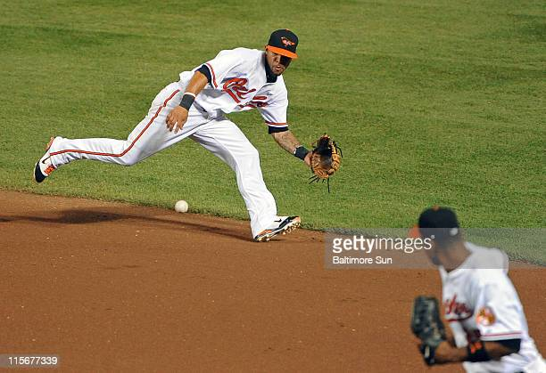 Baltimore Orioles second baseman Robert Andino top gets in position to field a grounder by the Oakland Athletics' David DeJesus before throwing to...