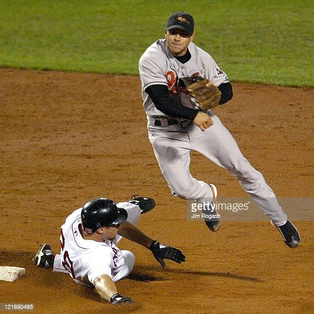 Baltimore Orioles shortstop Deivi Cruz turns a double play as Boston Red Sox base runner Gabe Kapler slides Thursday September 25 2003