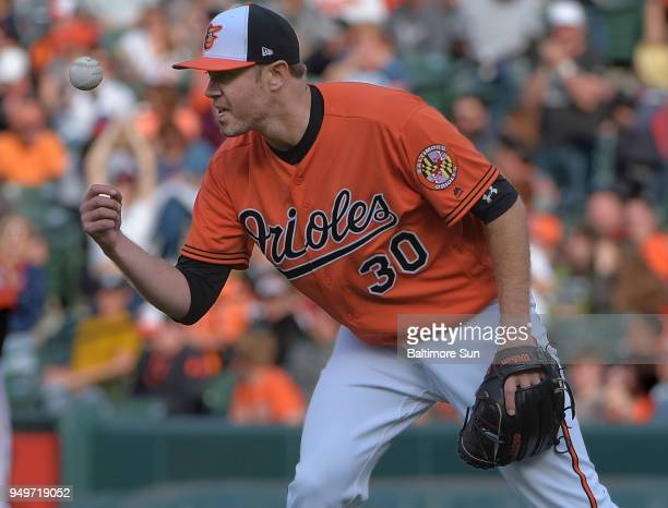 Baltimore Orioles starting pitcher Chris Tillman grabs a new baseball after yielding a solo home run to the Cleveland Indians' Yonder Alonso in the...