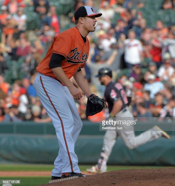 Baltimore Orioles starting pitcher Chris Tillman looks in as he Cleveland Indians' Yonder Alonso background rounds the bases following his solo home...