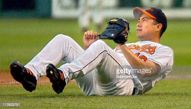 Baltimore Orioles' starting pitcher Rodrigo Lopez lies on the turf outside first base after tumbling while recording the out at the bag on a grounder...