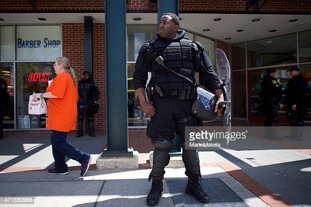 Baltimore police armed in riot gear monitor activity outside of a barbershop following days of citywide riots and protests regarding the death of...