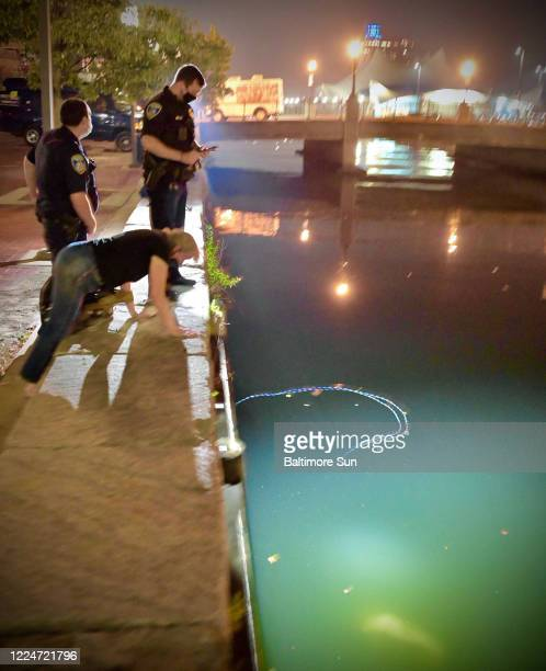 Baltimore Police look at the submerged statue of Christopher Columbus dragged by protesters into the southern end of the Jones Falls which drains...