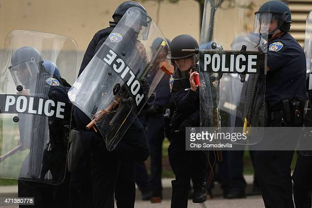 Baltimore Police officers protect themselves as protesters throw broken bricks at them outside the Mondawmin Mall following the funeral of Freddie...