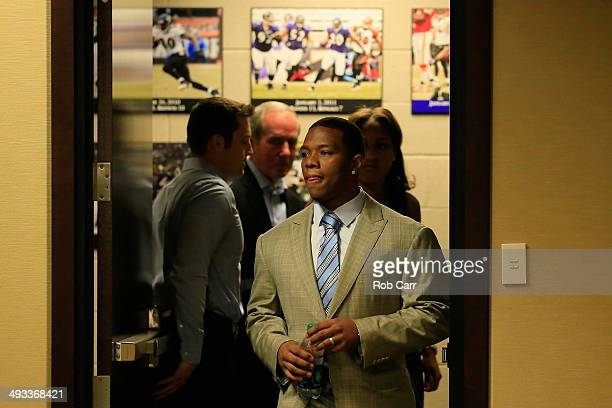 Baltimore Ravens assistant director of public relations Patrick M. Gleason holds the door as running back Ray Rice enter a news conference followed...
