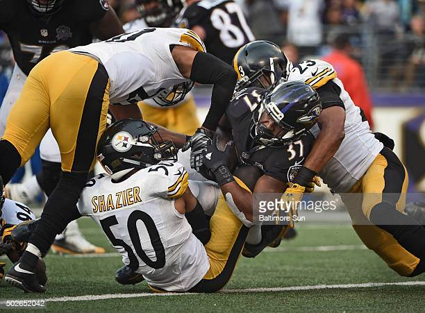 Baltimore Ravens' Buck Allen center crosses the goal line for a threeyard touchdown despite being surrounded by Pittsburgh Steelers' Ryan Shazier...