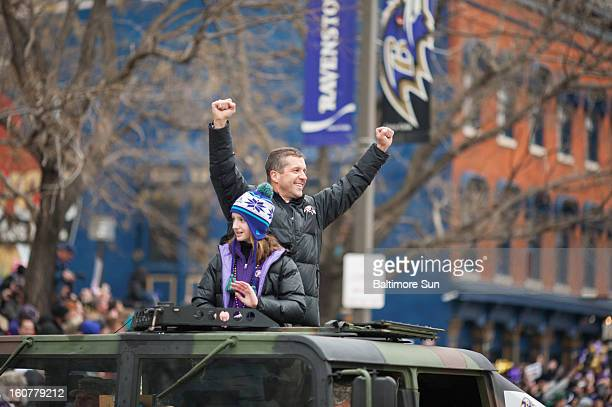 Baltimore Ravens head coach John Harbaugh and his daughter Alison wave to fans during a parade in Baltimore Maryland Tuesday February 5 2013
