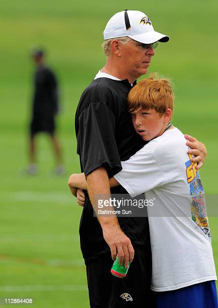 Baltimore Ravens offensive coordinator Cam Cameron and son Danny embrace during training camp at McDaniel College in Baltimore, Maryland, on...